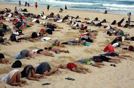 Australians bury heads in sand to mock government climate stance - Reuters