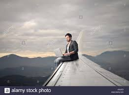 Man with laptop sitting on airplane's wing Stock Photo - Alamy