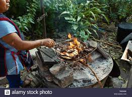 Outdoor kitchen with open fire. Zapotec woman roasting meat for dinner.  Teotitlan del Valle, Oaxaca State, Mexico. Apr 2019 Stock Photo - Alamy